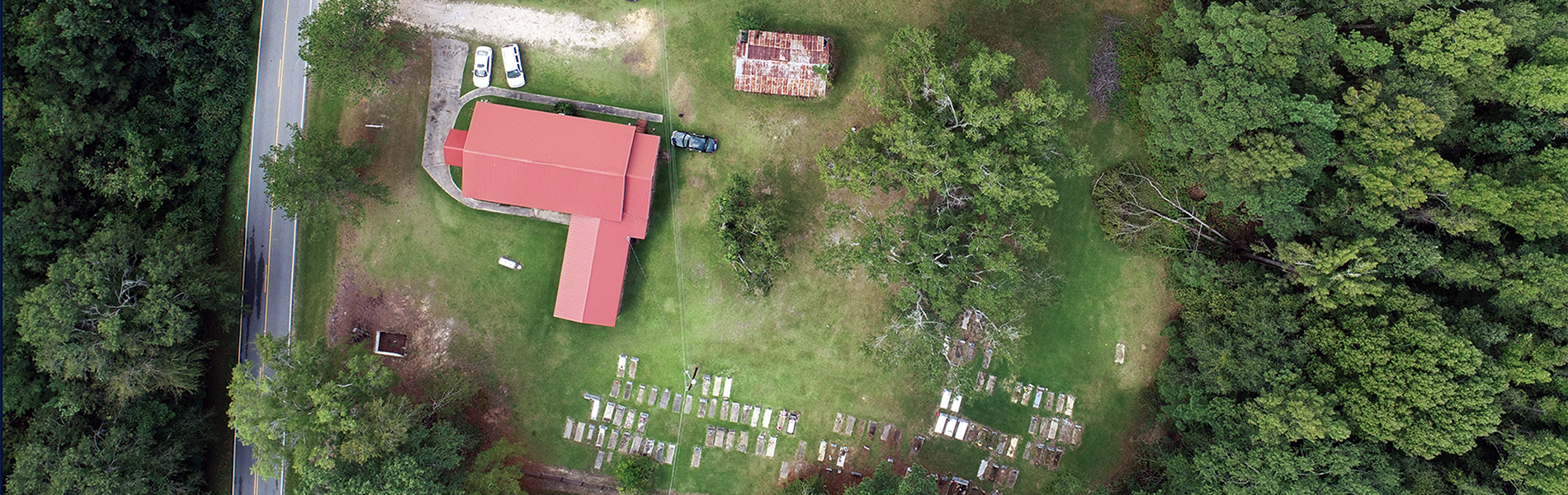 Birdseye view of grassy site with red-roofed L-shaped structure