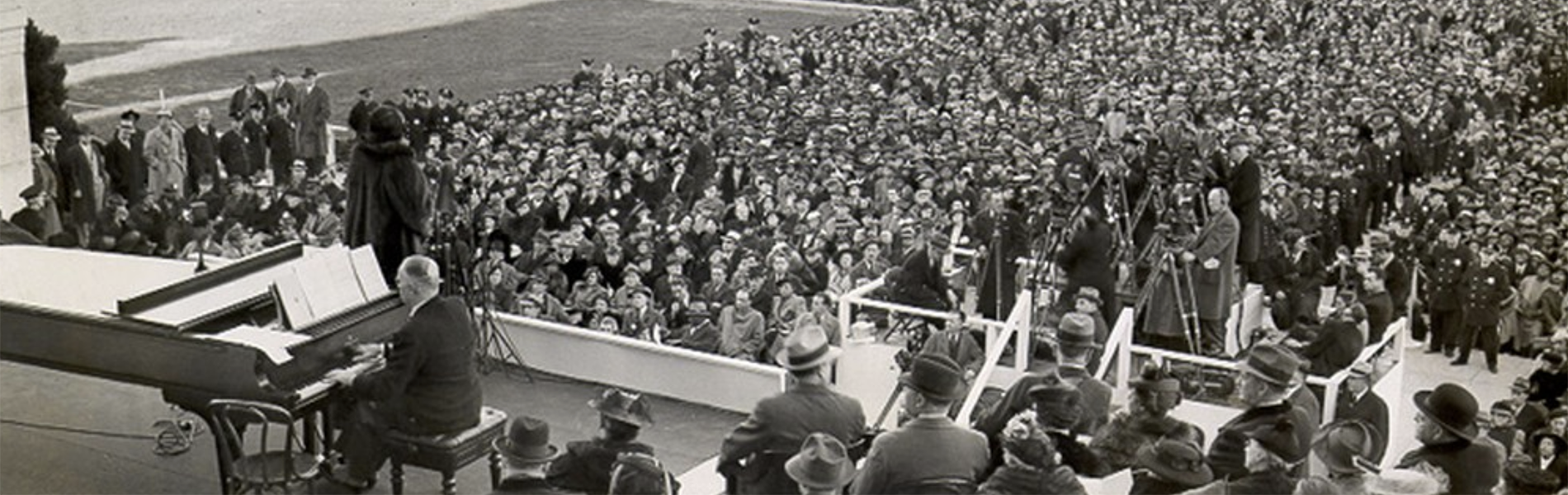 A sea of thousands of onlookers watch a singer in front of a piano in 30s era attire