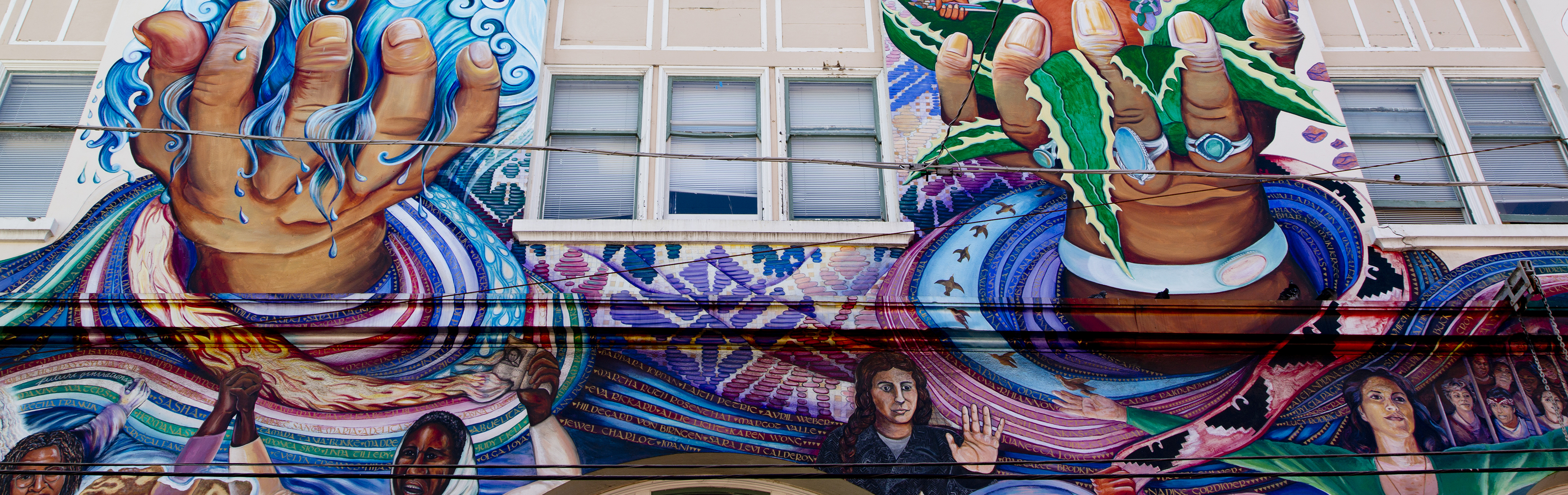 Outdoor mural in San Francisco depicting two hands and faces of Latina women