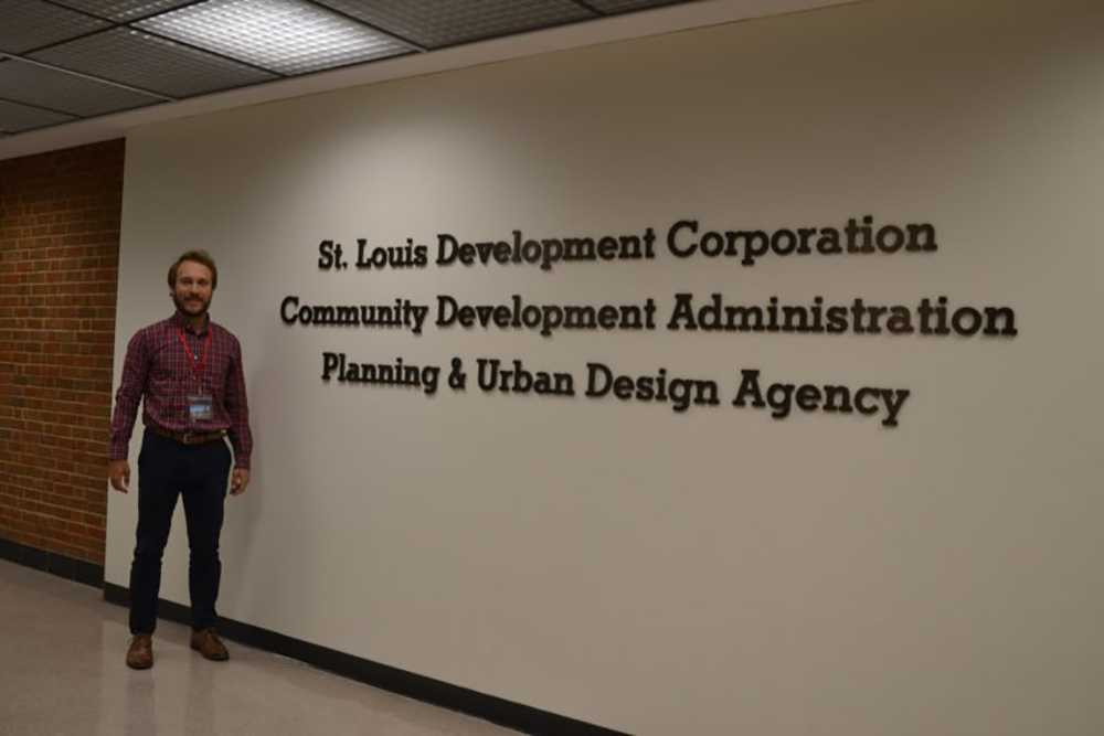Andrew Knop standing next to St. Louis Development Corporation sign