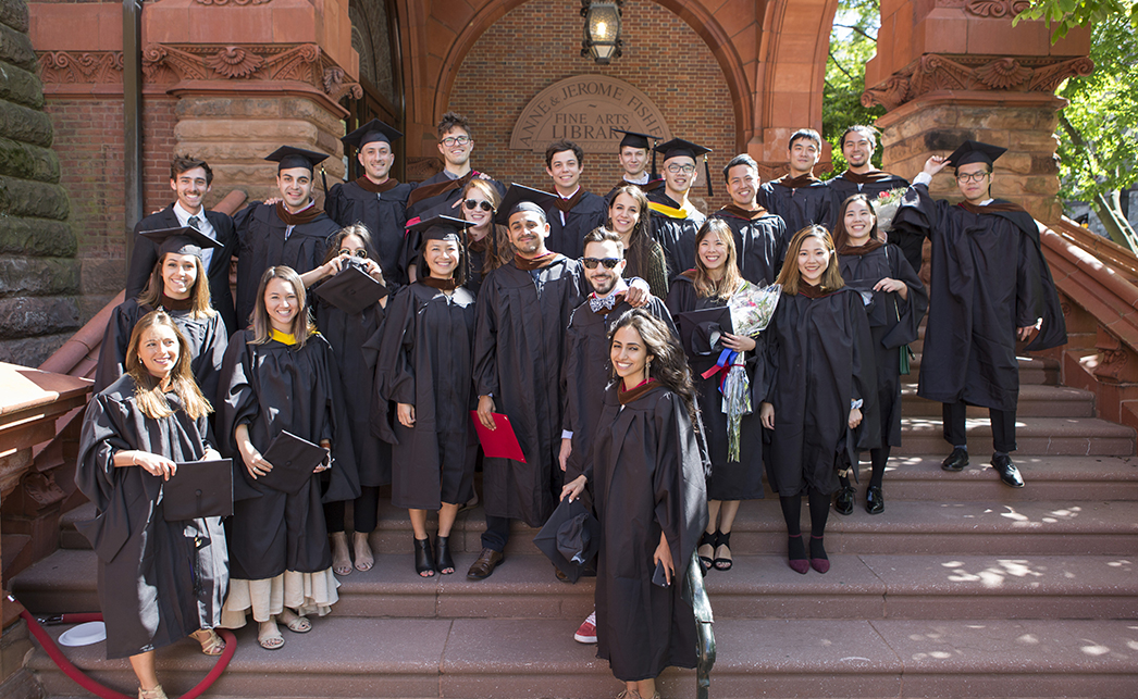 Photograph of Weitzman school graduates in regalia on the steps of the Fisher Fine Arts Library
