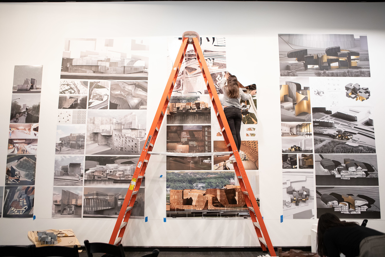 Student using a ladder to hang work on wall.