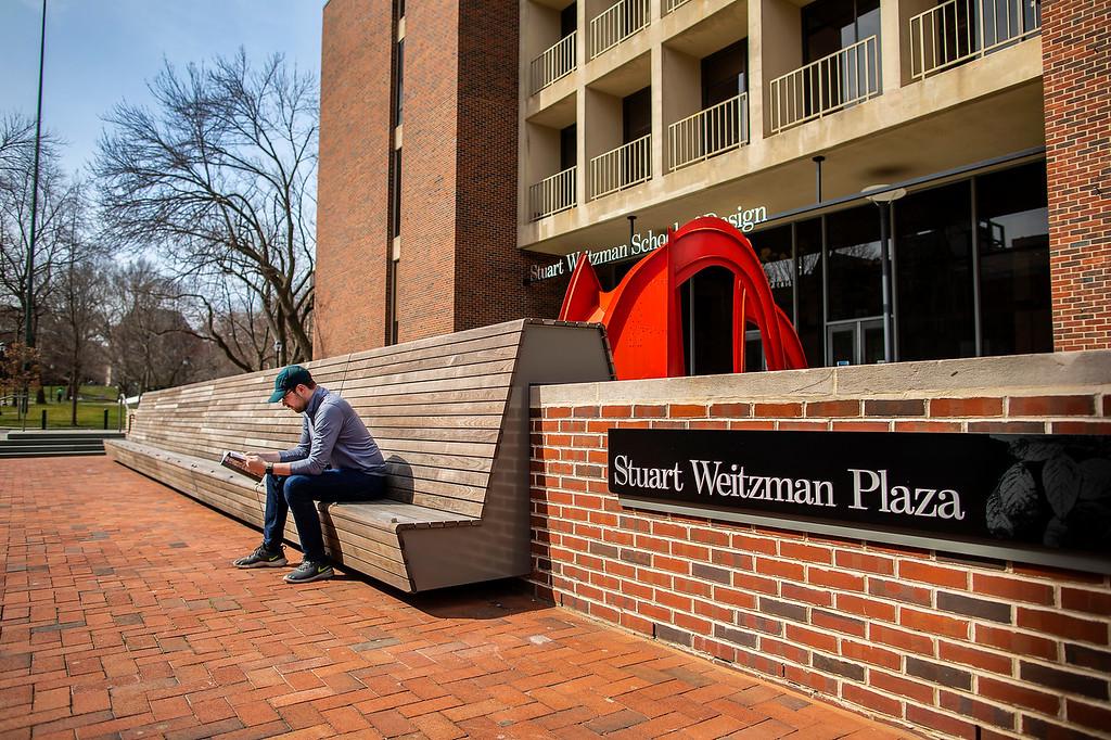 Man sitting on a bench in Stuart Weitzman Plaza