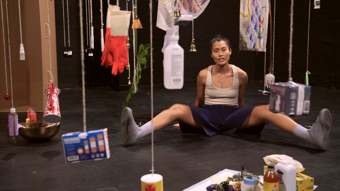Performer sitting on ground in black box, with hanging objects in the foreground to background