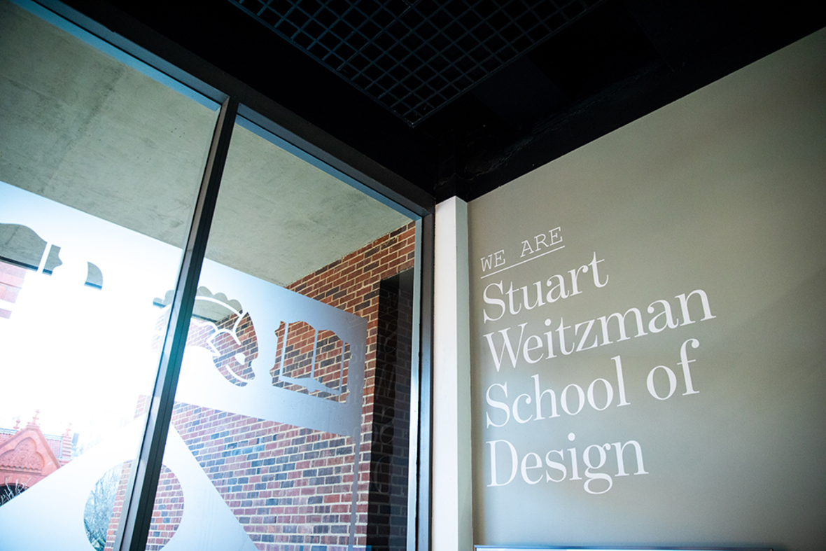 Picture of Stuart Weitzman logo on gray wall inside Meyerson Hall.