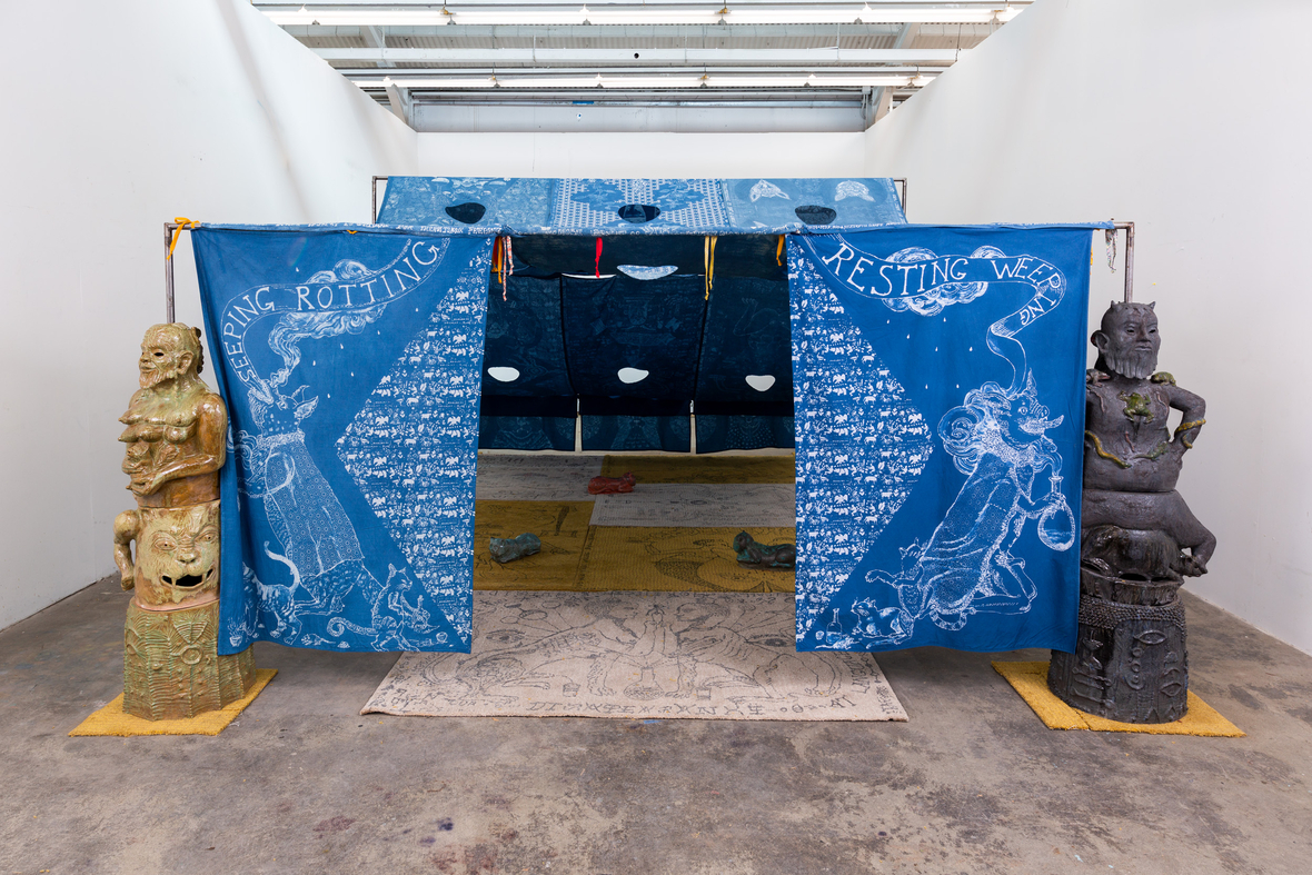 image of artwork installation, tapestry draped installation draws you into this space, two sculptures frame the entryway
