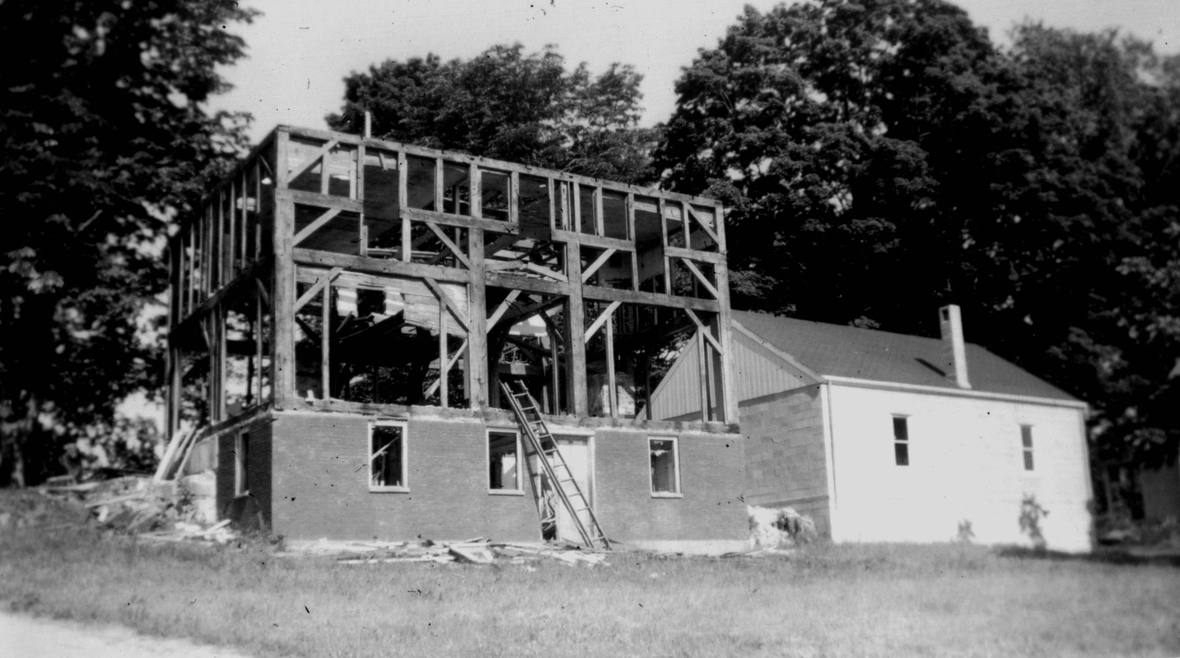 black and white photo of a house being built, 2 story wooden frame