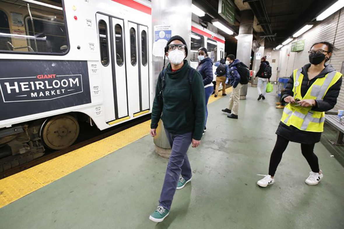 A masked man wearing glasses is walking through a trolley station