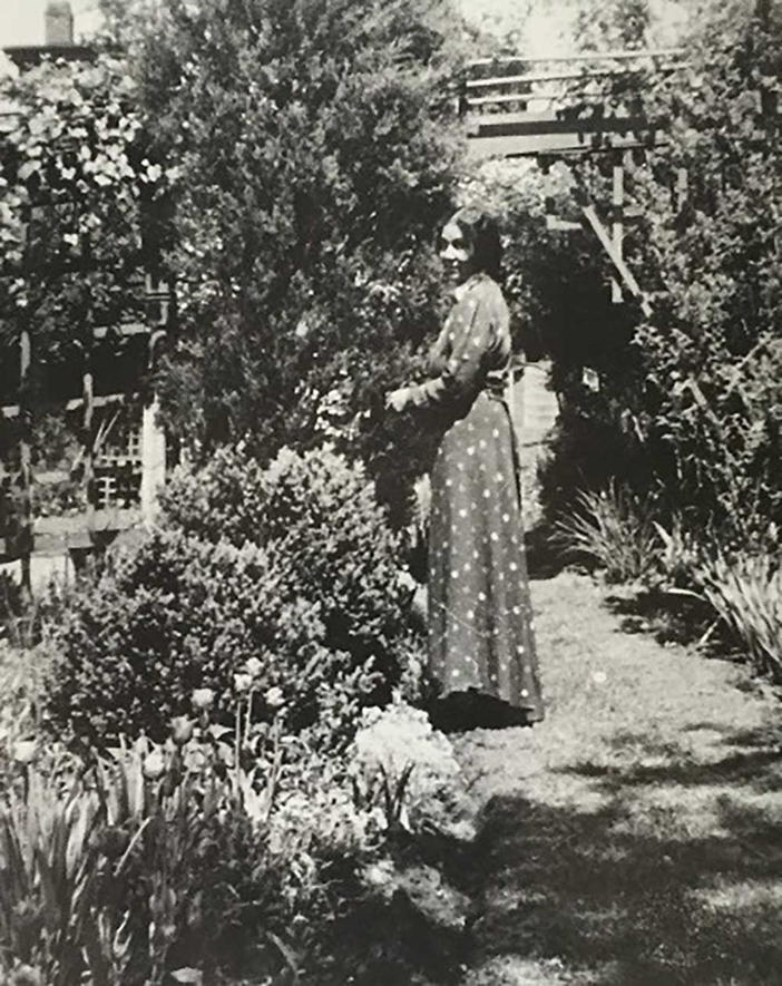 An old black and white photograph of a woman in a dress standing in a garden