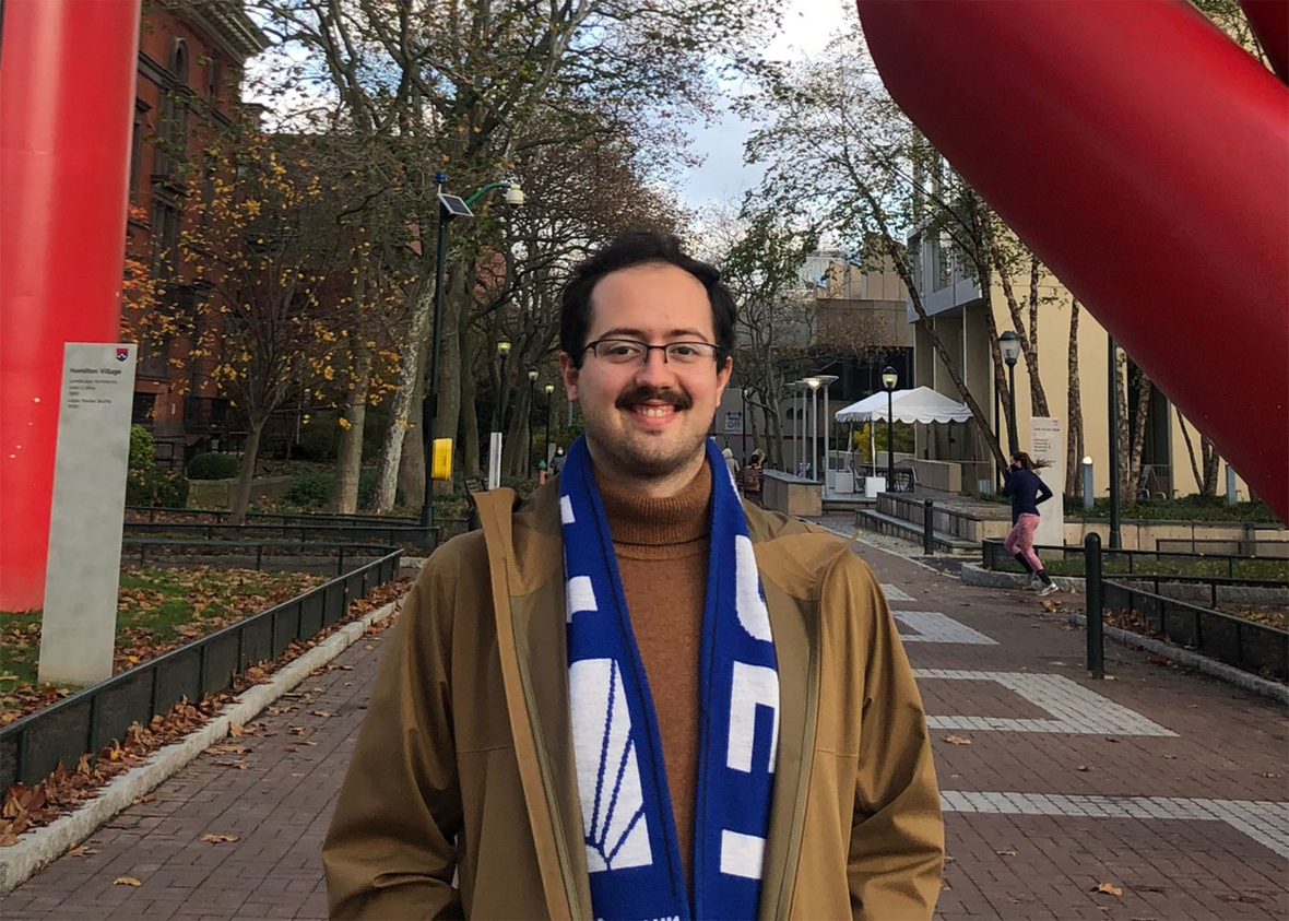 Michael wearing a blue scarf and tan coat on Locust Walk