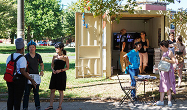 A group of young people standing outside a shipping container in a park