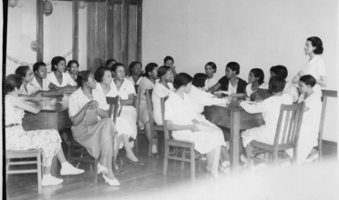 B&W photo of group of women having meeting around several tables