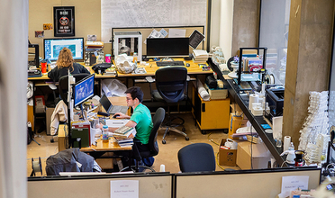 Two students working at their desk are seen from above in the studios at Meyerson Hall
