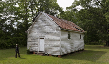 Weathered single-story white wood-sided structure with red roof in a wooded setting