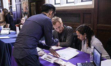 A student stands over a table showing his work to employers