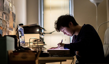 Dennis Kim draws at his desk with printed images on the wall he faces