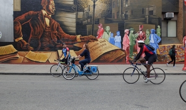 People riding bicycles in front of a mural.
