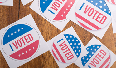 """Round red, white, and blue """"I VOTED"""" stickers on a wooden table"""