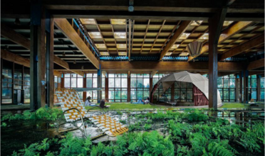Lawn chair in foreground surrounded by lush greenery in an indoor warehouse with tent in background