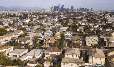 Aerial view of single family homes with downtown skyline in background