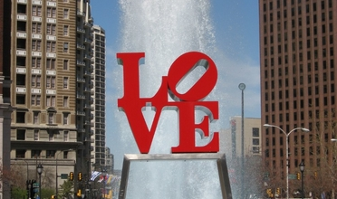 LOVE statue in Love park with fountain behind.