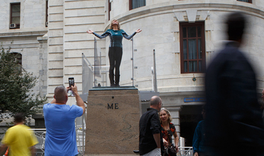 A woman stands on a pedestal outside Philadelphia City Hall