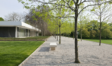 A modernist house with a gravel walkway and bench in front