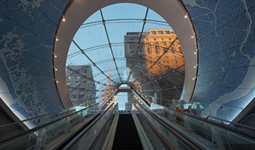 An escalator to the street features a glass oculus surrounded by a map of NYC in tiles