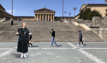A woman in black attire stands on an outdoor staircase with the museum in the background