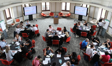Bird's eye view of people seated at six round tables in discussion