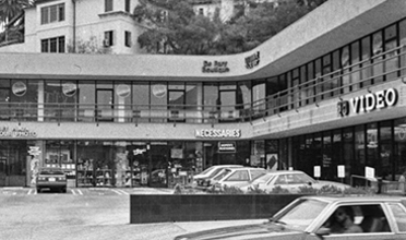 Black and white photo of 3-story drive-up shopping mall