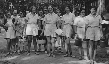 A group of women dressed in white uniforms pose for a 1934 photograph.