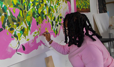 Patricia Renee Thomas works on a neon-palette landscape painting mounted to the wall.