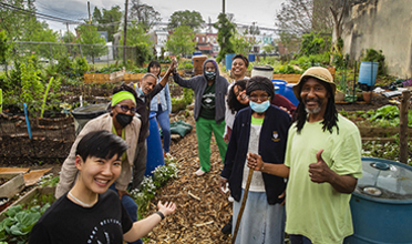 A group of people of various ages and ethnicities stand in a community garden