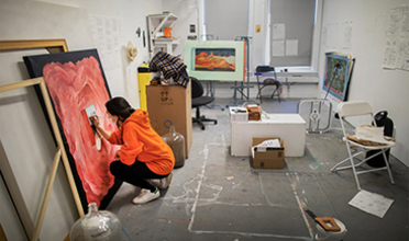 Woman painting on canvas in orange hoodie and blue jeans