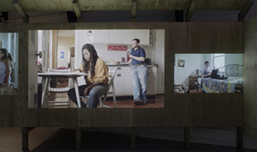 Installation shot of video installation, video showing two people in a kitchen, one of them sitting at a table