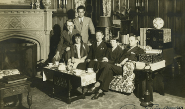 Black and white image of group seated on sofa in wood paneled room