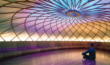 A man sits on the floor of a circular room the ceiling of which is a complex radiating structure