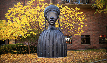 Large sculpture of a woman seen against autumn trees