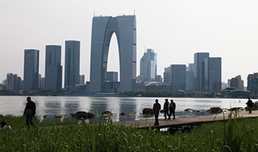 Park along a waterfront with a modern skyline on the opposite shore