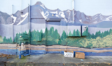 Exterior of the rear of a commercial building painted to resemble a mountainous landscape