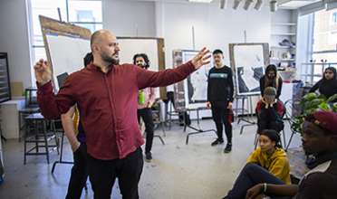 A man leads a discussion with students in an art studio
