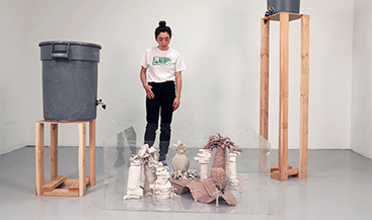 Image of the artist with installation made of varied materials