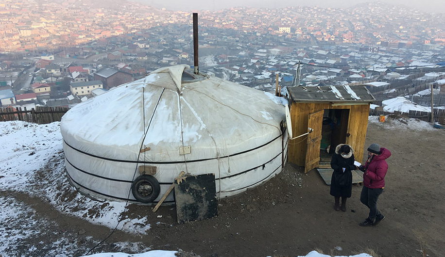 Two women stand outside a white tent dwelling with city in the background