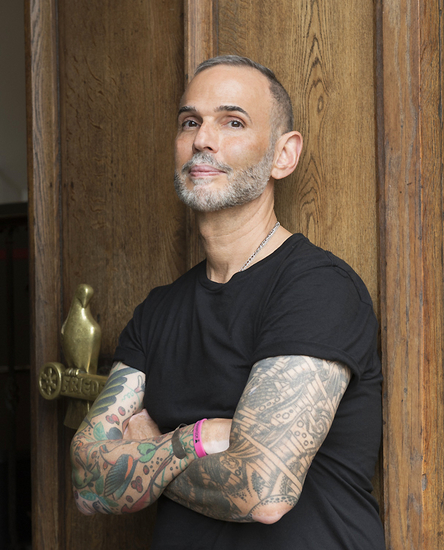 Headshot of Ernesto w heavily tattooed crossed arms, leaning against a wooden door frame