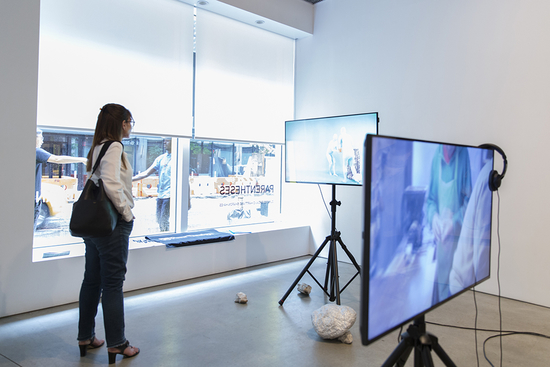 Video art pieces in gallery with student observer