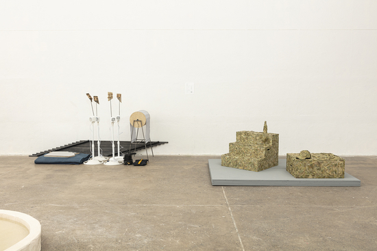 open gallery installation with concrete floor, featuring sculptures by students