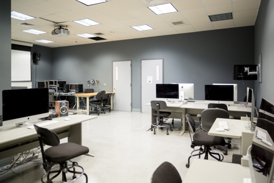 Brightly lit unoccupied computer lab with screen and projector