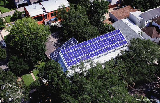 Solar panels cover a rectangular building surrounded by trees