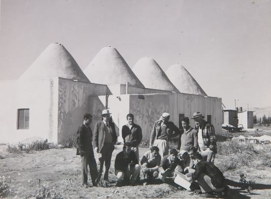 B&W photo of people standing outside of building with several conic structures for a roof